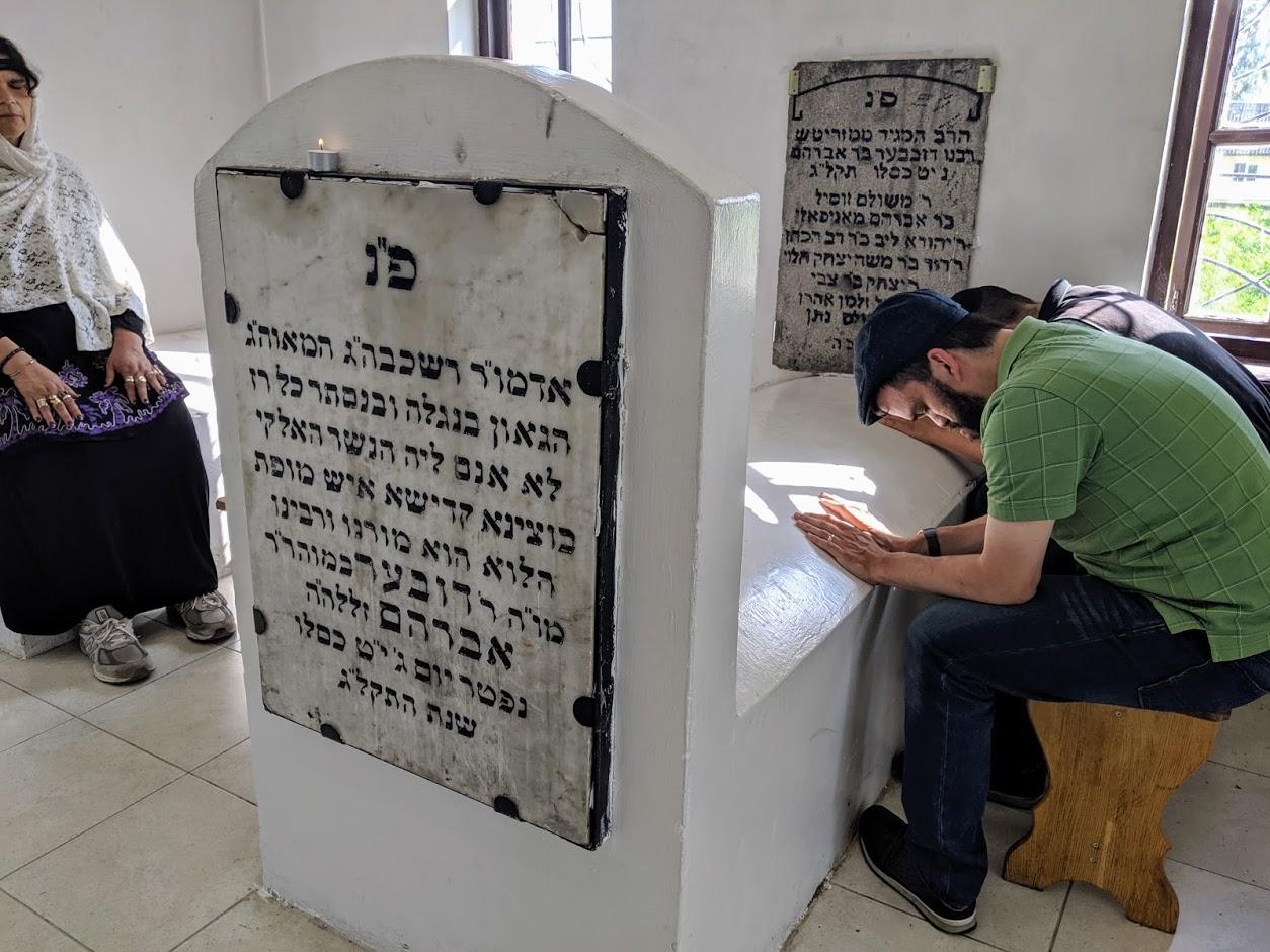 praying at hasidic grave