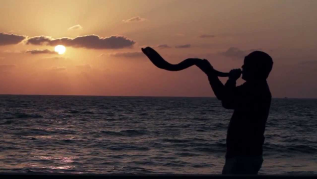 man blowing shofar at sunrise