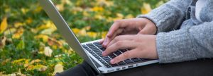 person with laptop on fall grass
