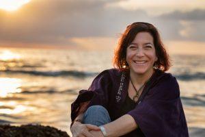 Amy Grossblatt Pessah sitting on a beach